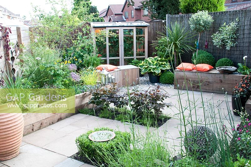 Suburban courtyard garden with wooden block seats and bench