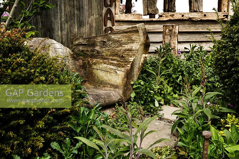 Weathered wooden seat with naturalistic planting and stepping stones - Macmillan Legacy Garden - RHS Malvern Spring Show 2016
