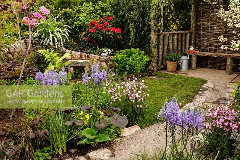 Rustic stone and gravel path leading to seating area through mixed colourful planting including Camassia - Camas lily - The Water Spout garden - RHS Malvern Spring Show 2016. Designer: Christian Dowle. Sponsor: Garden Inspiration