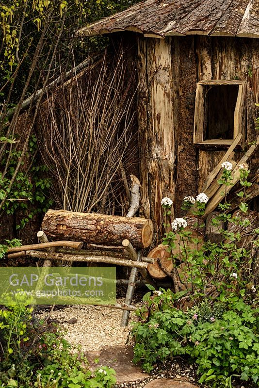 Rustic wooden hut, saw horse, logs and woodland planting - The Woodcutter's Garden - RHS Malvern Spring Show 2016. Designer: Mark Walker, Sponsor: Howards Motors