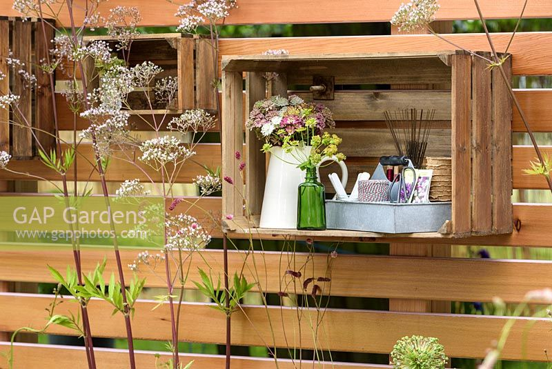 Decorative flower displays in crates used as shelves on the wooden panel fencing. Katie's Lymphoedema Fund: Katie's Garden, RHS Hampton Court Palace Flower Show 2016. Design: Noemi Mercurelli and Carolyn Dunster