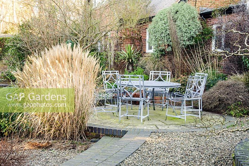 Seating Area At The Back Of House Surrounded By Planting Including Gres Such As Miscanthus
