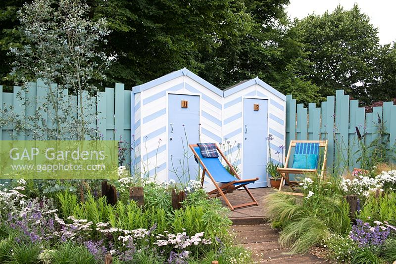 Blue and white painted beach huts with deck chairs on decking, Eucalyptus gunnii 'Azura' underplanted with Achillea millefolium 'Wonderful Wampee', Nepeta racemosa 'Walker's Low', Verbena bonariensis, Stipa tenuissima - By The Sea, RHS Hampton Court Palace Flower Show 2017