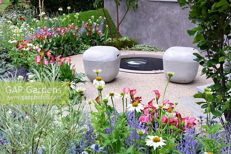 On The Edge -The Centre For Mental Health garden. Colourful Borders around graveled seating area with tone chairs and circular reflecting pool. Designers: Frederic Whyte RHS Hampton Court Palace Flower Show 2017