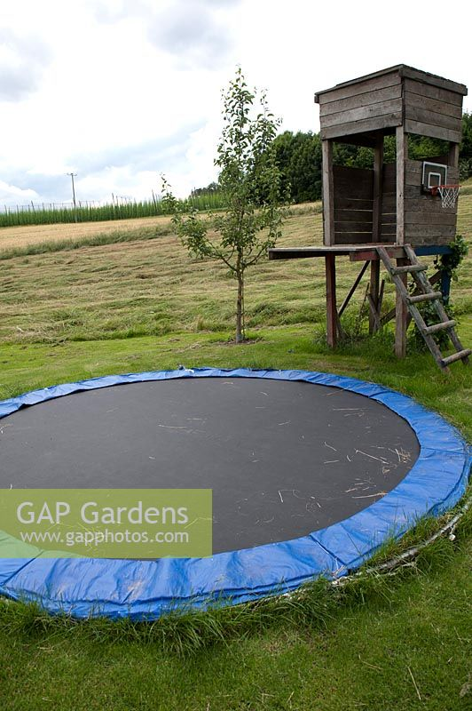Children's play area with trampoline sunk in the ground