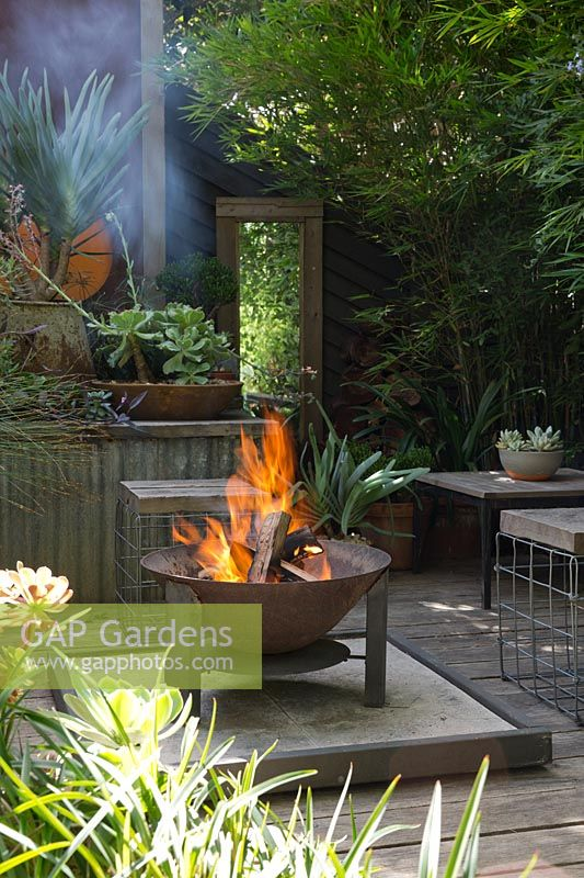 A sunken fire pit area with a freestanding metal fire pit, on a timber deck surrounded by raised garden beds and rusty corten steel screens.