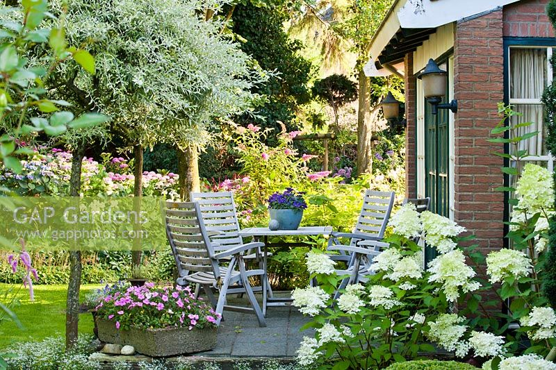 Relaxing area on a patio. Hydrangea paniculata Phantom, Salix. Design: Laura Dingemans