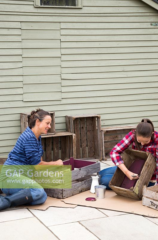 gap gardens woman and young girl painting inside of wooden crates