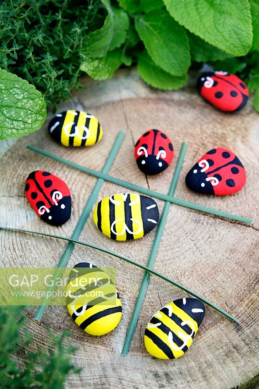 Garden craft making painted Bumble bees and Ladybirds with stones. Long grasses laid out to make a noughts and crosses board