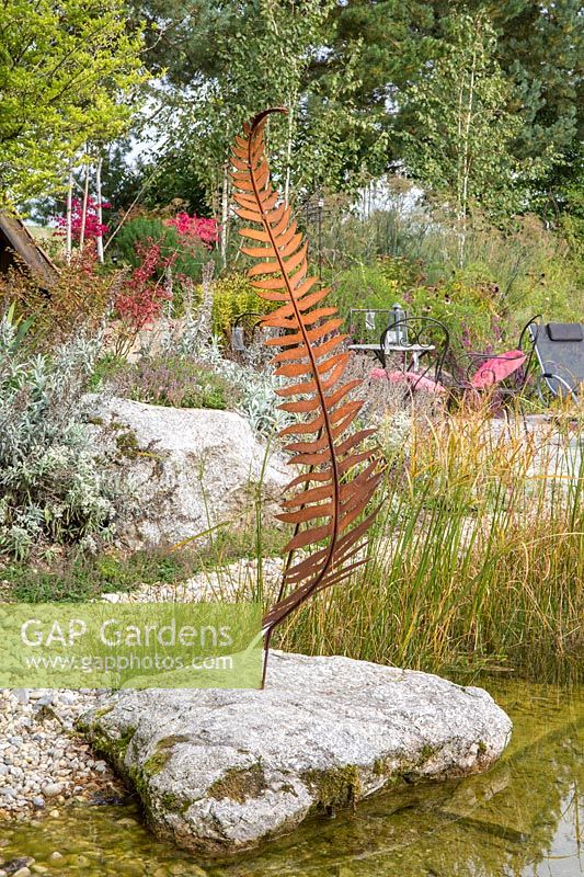 Next to the shallow water zone a metal sculptural fern on a granite boulder. In the background a rest area, birches and perennial planting