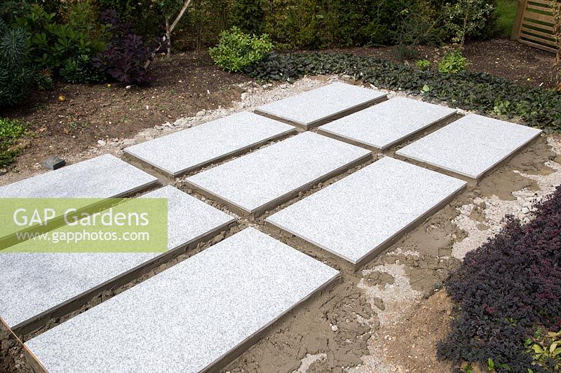 Making a mixed material patio - grid of large porcelain slabs ready to infill with granite setts
