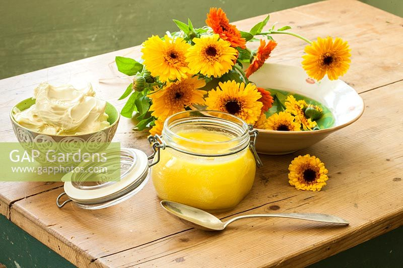 On a wooden table, a preserving jar filled with Calendula balm and flowers in a bowl