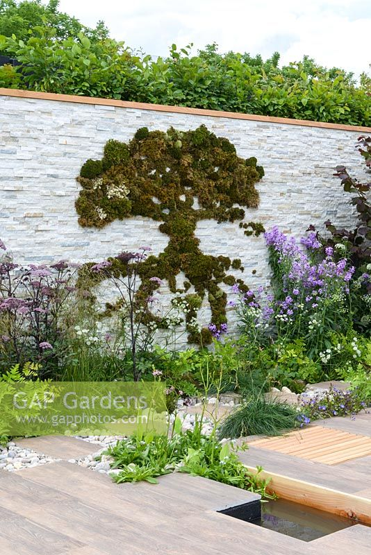 Moss graffiti of tree on stone wall and planting along white gravel and natural stone path -  BBC Gardener's World Live, Birmingham 2017 - Big Fish Landscapes Garden -Designer: Cherry Carmen, Cherry Carmen Garden Design -Gold