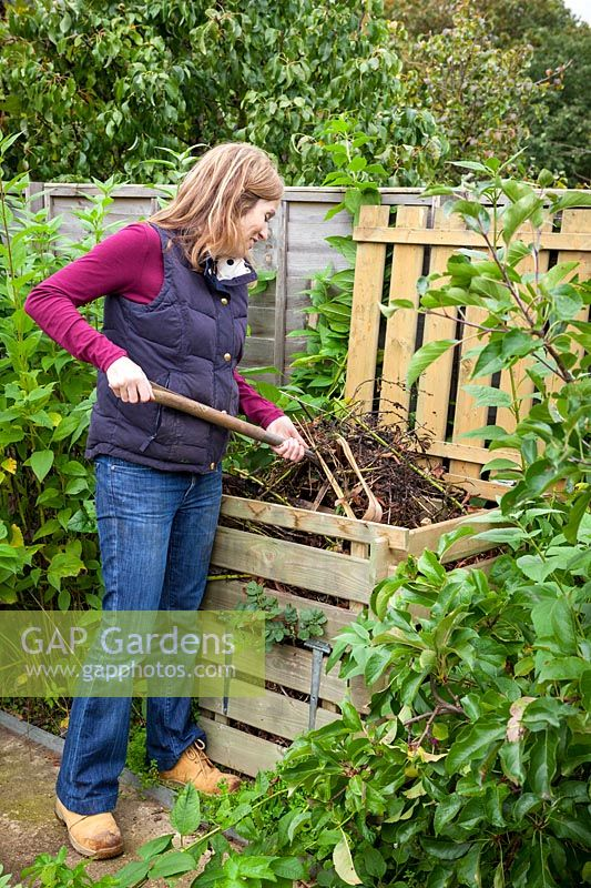 Turning over compost heap with fork to speed up process of decomposition, October