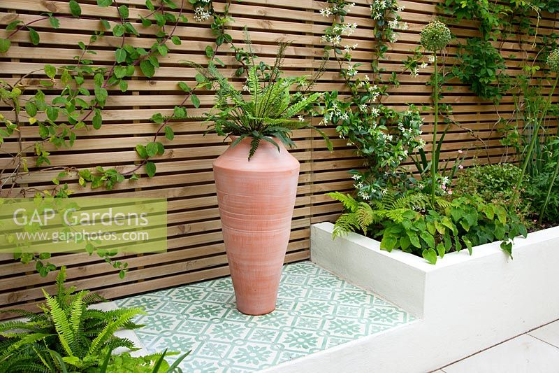 Plinth paved with morroccan tiles and raised beds of ferns, with large oil jar and slated trellis, June