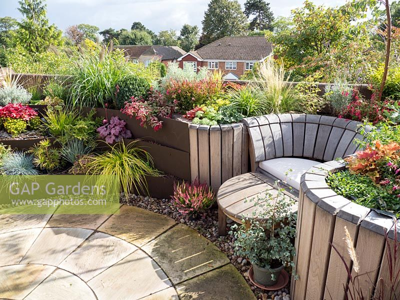 Balcony garden with tiered planting, circular stone patio and wooden seat.