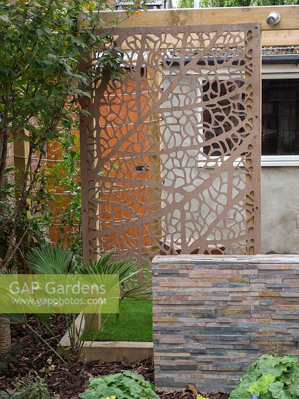Cut metal screen adds depth to small garden still keeping it light and airy