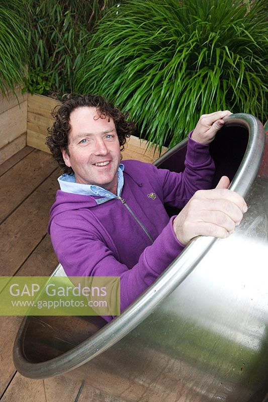 Diarmuid Gavin entering the stainless steel shute of his Westland Magical Garden, Chelsea Flower Show 2012