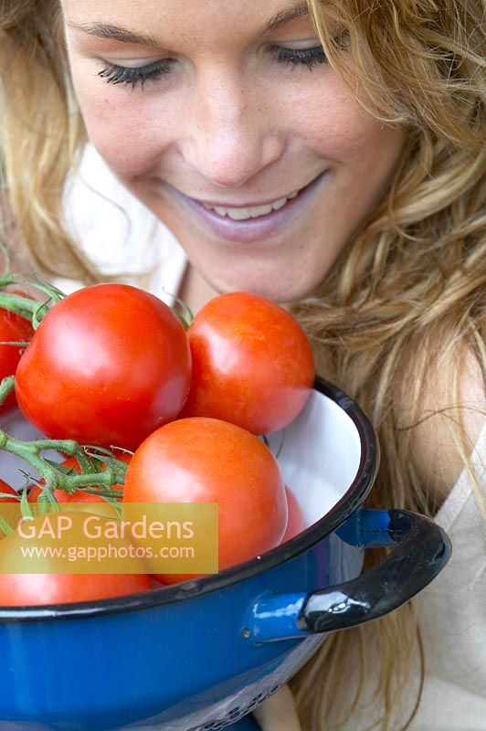 Woman holding colander with tomatoes