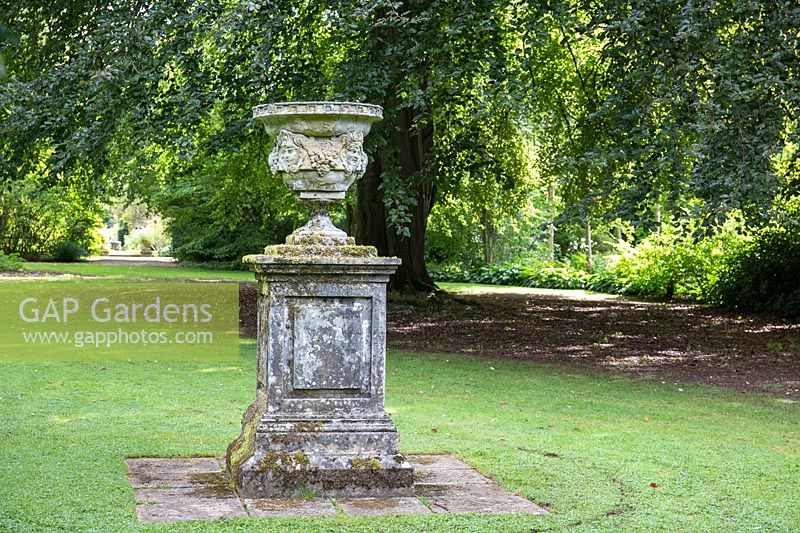 A stone pillar and urn with antique carving on lawn at Newby Hall and Gardens, Yorkshire.
