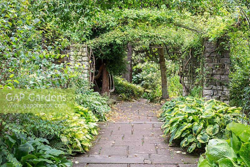 A view of a flagstone paved garden and archway at Newby Hall and Gardens, Yorkshire.