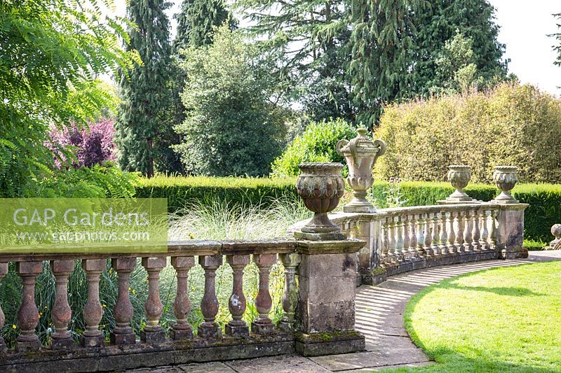 Stone balustrade with antique styled urns look over grasses and Taxus baccata - Yew - hedge, Newby Hall and Gardens, Yorkshire.