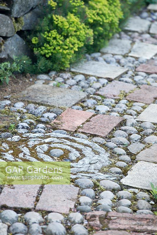Close up of ornate path made with patterns of pebbles and paving slabs.