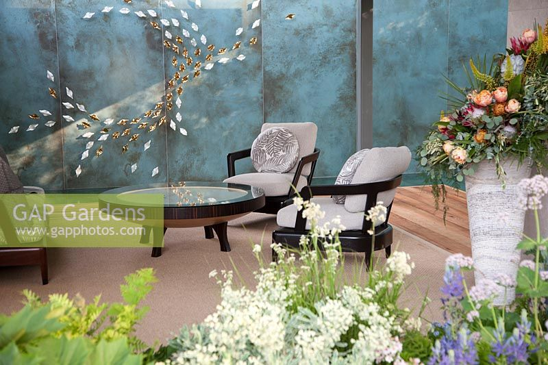 The Morgan Stanley Garden for the NSPCC - Seating in garden room with wall decoration reflected in table top - Sponsor: Morgan Stanley - RHS Chelsea Flower Show 2018