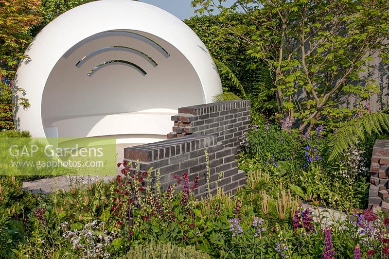 Space to Grow Garden - The CHERUB HIV Garden: A Life Without Walls - white pod representing a clinic, mixed planting and broken walls - Sponsor: CHERUB - RHS Chelsea Flower Show 2018