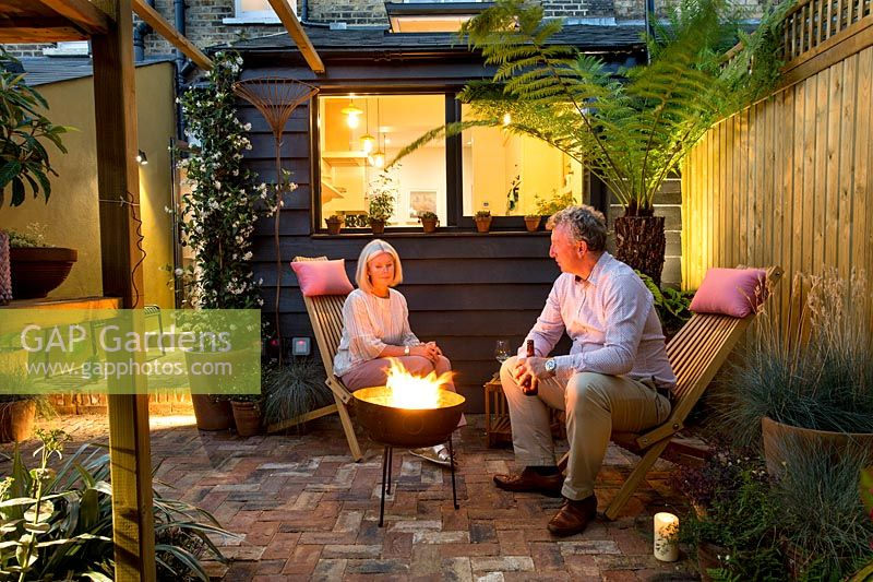Owners Emma and Brian sitting next to fire bowl in their small London patio garden