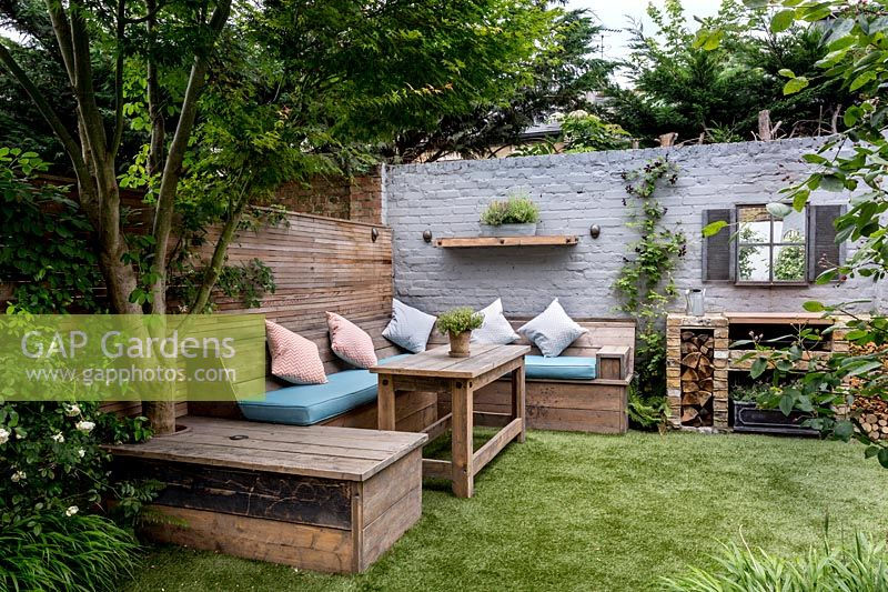 Small courtyard garden in West London with artificial lawn, built in Reclaimed 