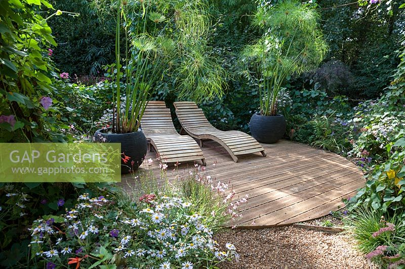 Twin wooden seats on decking with mixed planting. Pensees Jardinieres, 