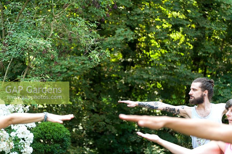 Yoga in a green garden. 4 people are in the position Virabhadrasana II