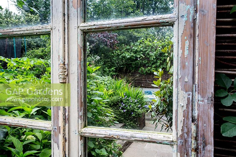 Reclaimed mirror with reflections of North London garden and patio.