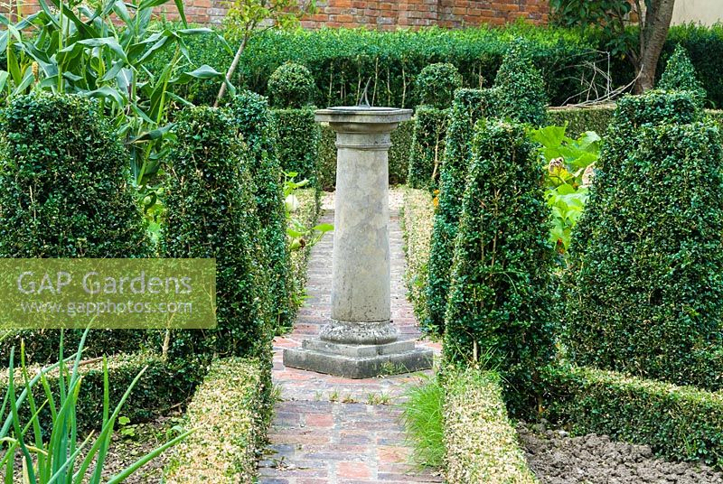 Walled kitchen garden with box edged beds and central sun dial.