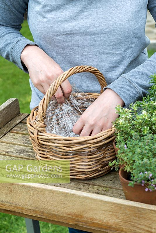 Woman lining a wicker basket ready to plant with herbs.