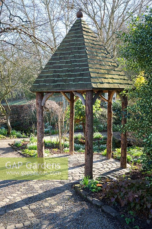 Wooden gazebo with slate roof at York Gate garden, Leeds, UK.