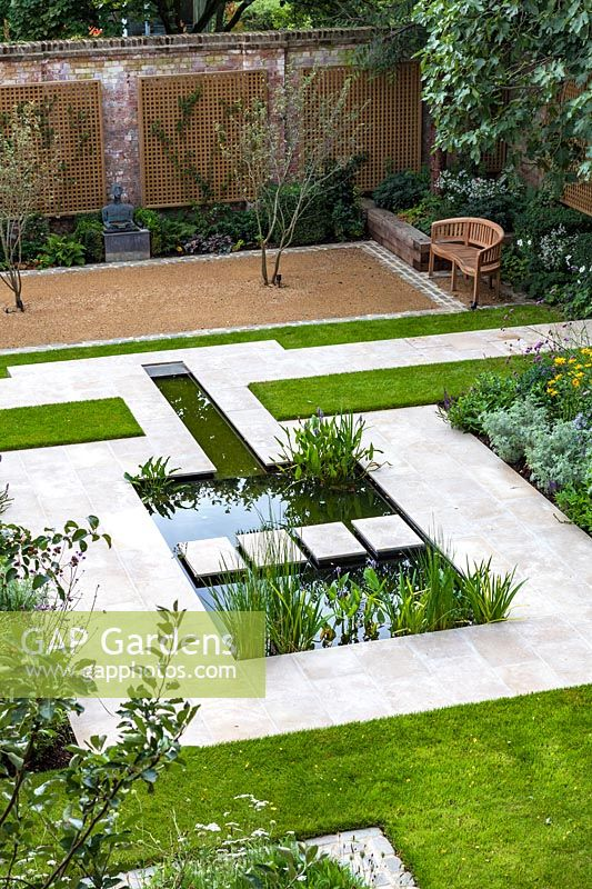 Overview of formal pond and stepping stones in walled city garden. Garden design by Peter Reader Landscapes.