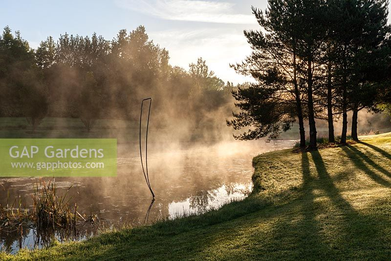 Mist rising from the lake with metal sculpture at sunrise. Plaz Metaxu Garden, Devon, UK.