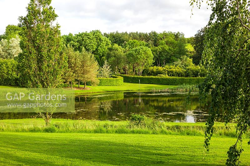 Lake surrounded by trees and lawn. Plaz Metaxu Garden, Devon, UK.