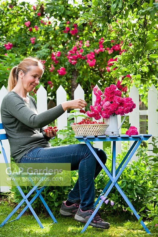 Woman enjoying cherries in the garden.