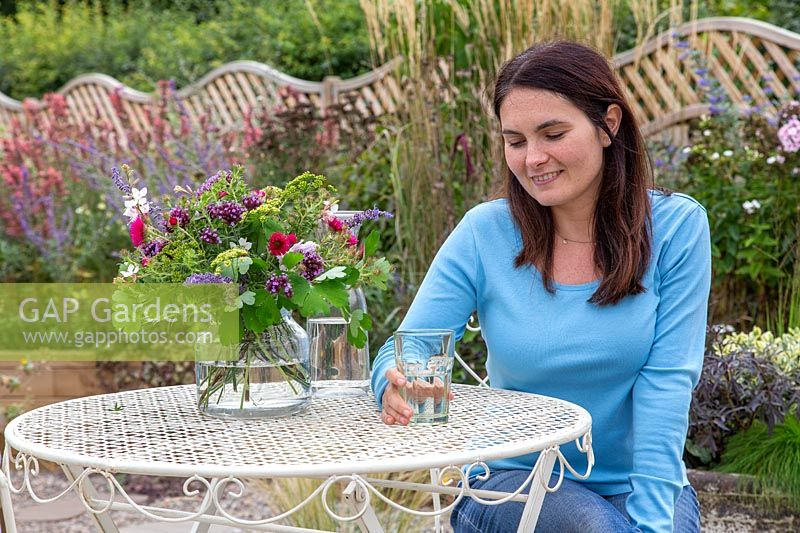 Woman sitting at metal table with glass of water and vase of cut flowers.