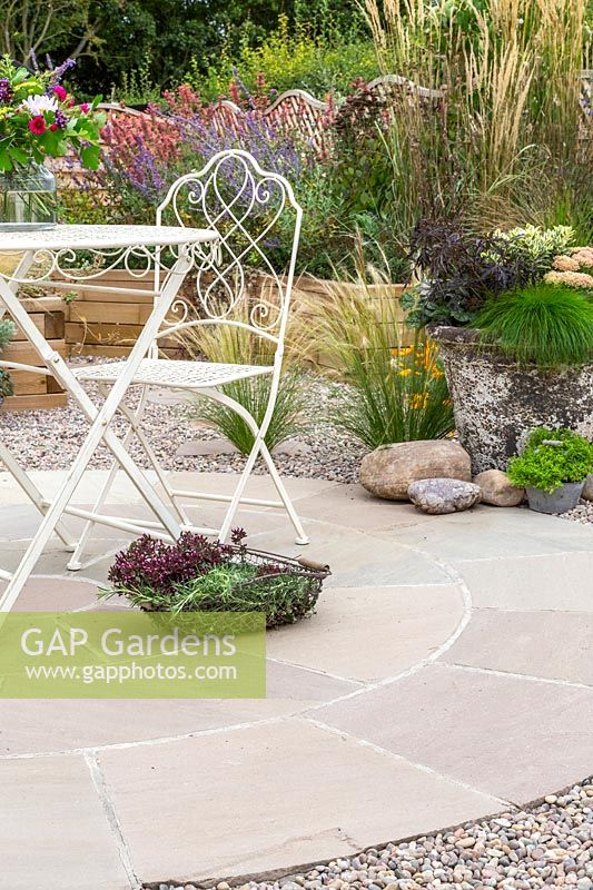 Ornate metal table and chair on circular patio in gravel garden