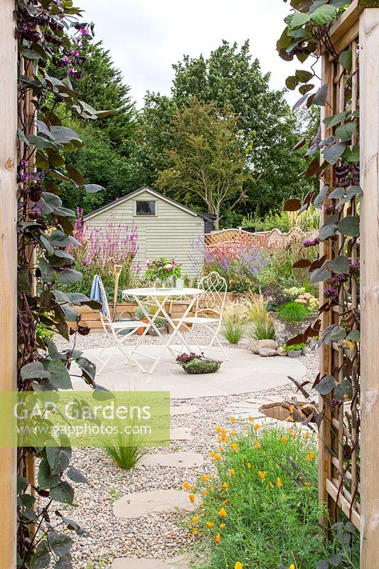 View through wooden arch towards metal table and chairs on circular patio