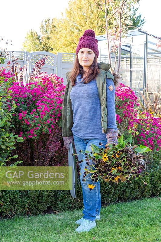 Woman standing in front of flowering Aster with trug of cut seed heads from the garden