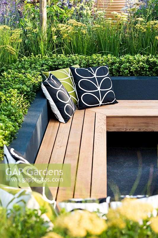 Modern seating area with benches surrounded by raised flower beds. Best of Both Worlds garden, Sponsored by BALI, RHS Hampton Court Palace Flower Show, 2018.