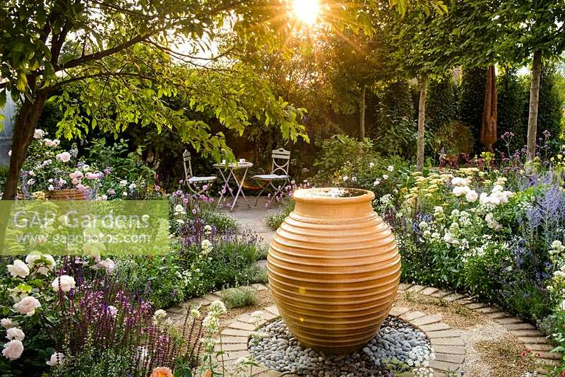 Circular paving around water feature surrounded by borders with summer flowers. Best of Both Worlds garden, Sponsored by BALI, RHS Hampton Court Palace Flower Show, 2018.
