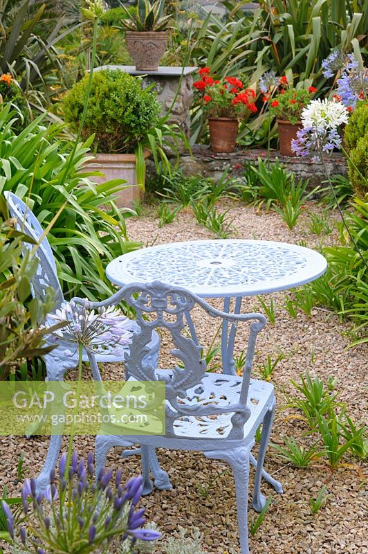 Ornate table and chairs in gravelled terrace, surrounded by flowering perennials and potted plants.