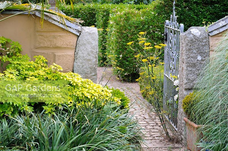 Stone path and gate with self seeded fennel.