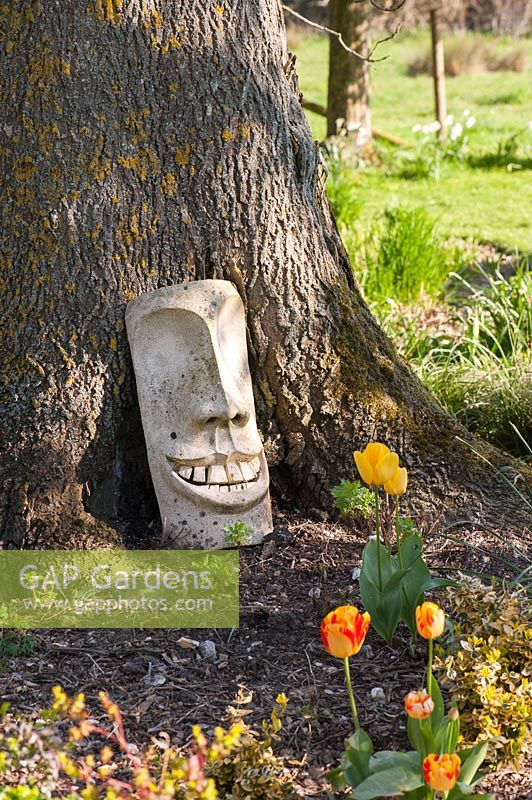 Ceramic sculpture of face on tree trunk, Stockbridge, Hampshire